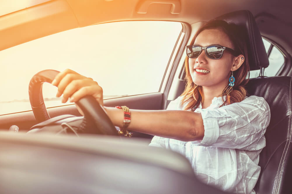 happy woman driving a car with insurance