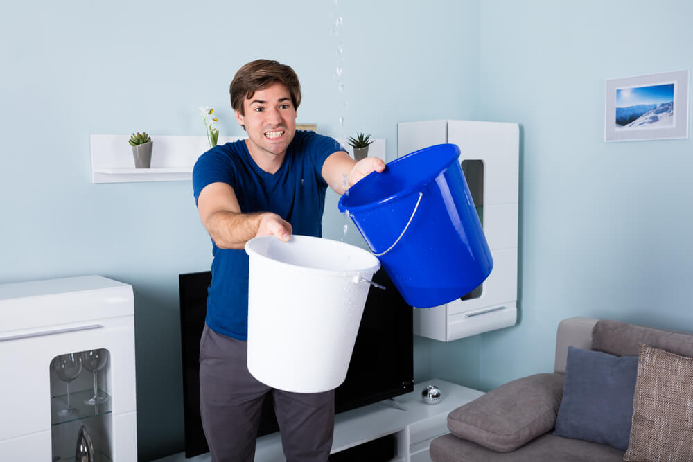 man in apartment gathering water from leak with two buckets