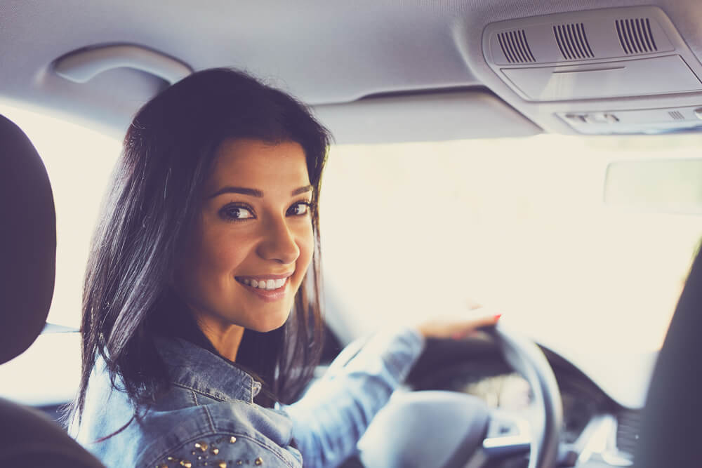 Smiling woman sitting in a car and looking bac