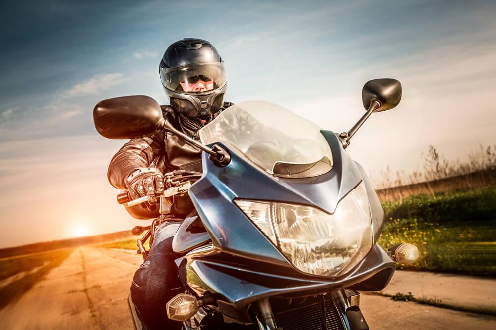 man riding motorcycle wearing helmet on the road