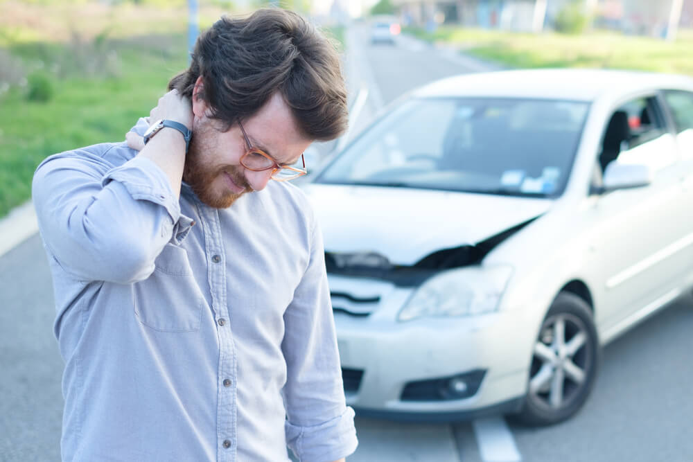 hurt man grabbing his neck in front of crashed car hit and run