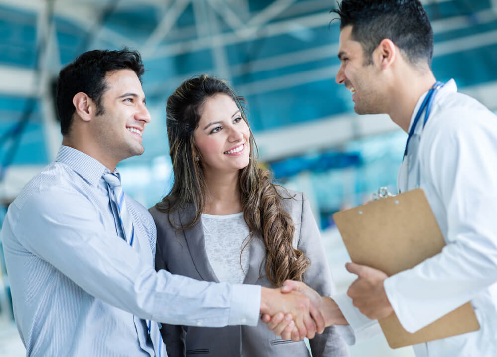 happy couple shaking hands with doctor indemnity plan insurance