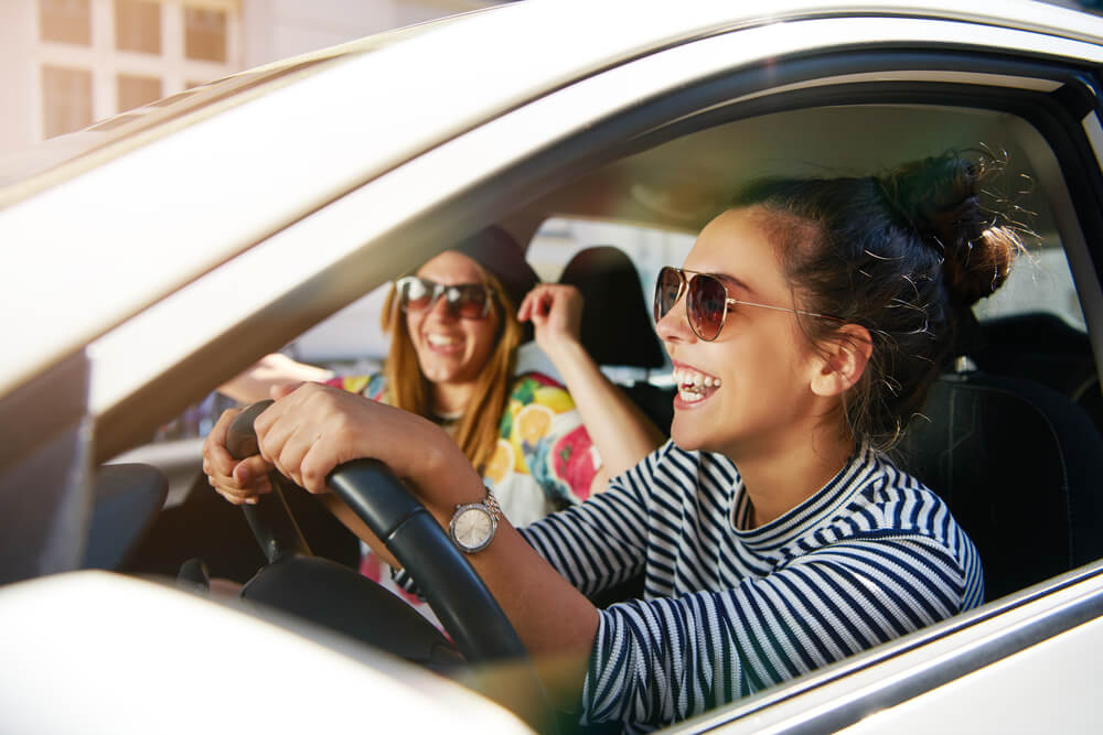 young happy women driving a car with non owner insurance