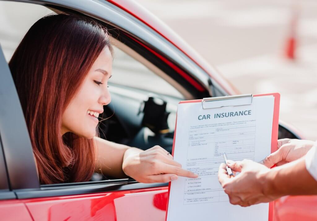 woman in rental car signing insurance form