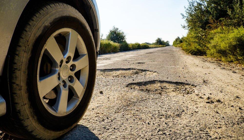 car tire next to potholes on highway avoid potholes