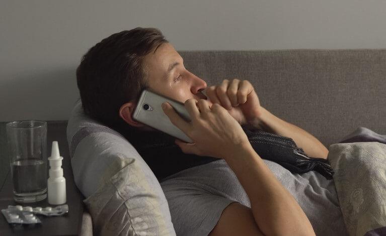 man sick in couch calling a doctor telemedicine coronavirus