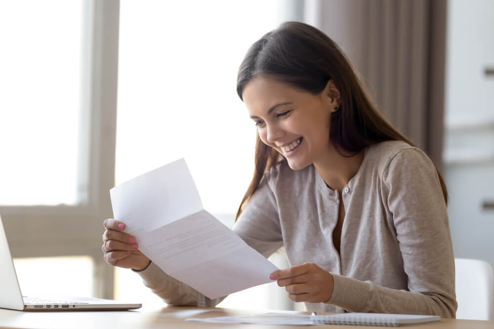 smiling woman reading a letter while social distancing