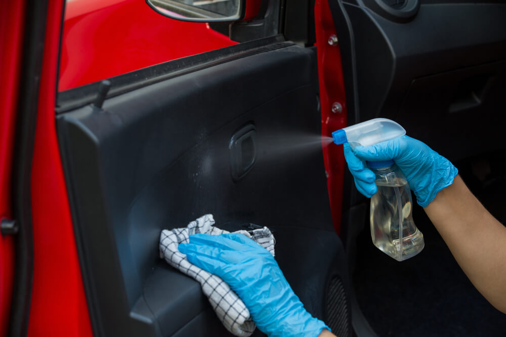 hands with gloves disinfecting a car door with spray