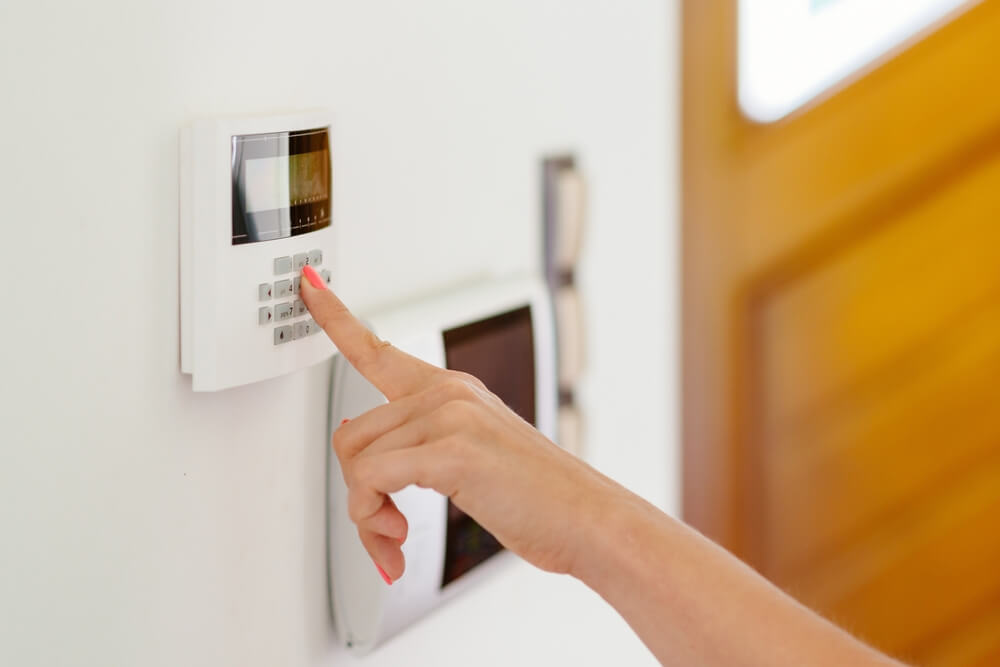 hand inputting a security code on a home security system to prevent theft