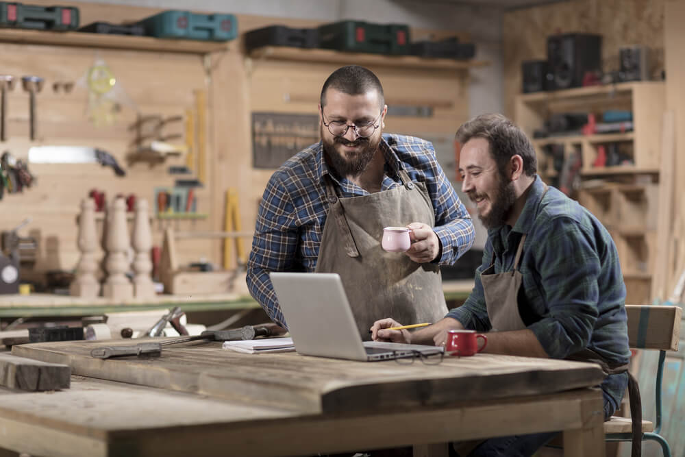 woodworkers at their shop looking at a business insurance policy in a laptop