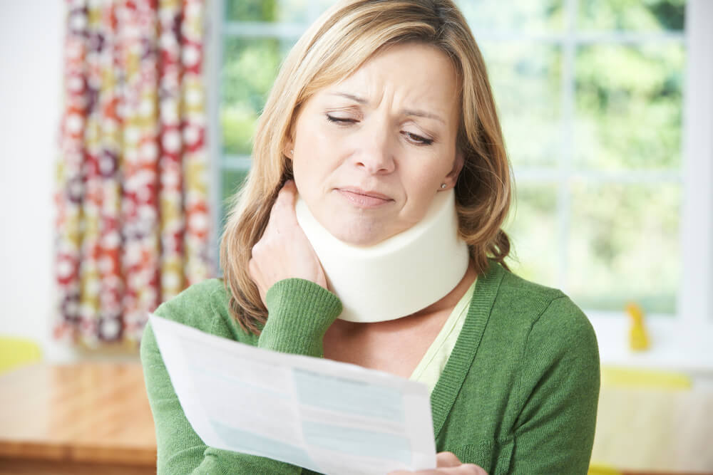 woman with a neck injury from a car accident looking at her medical bill