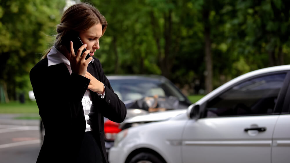 worried woman using her phone after a car accident with an uninsured driver