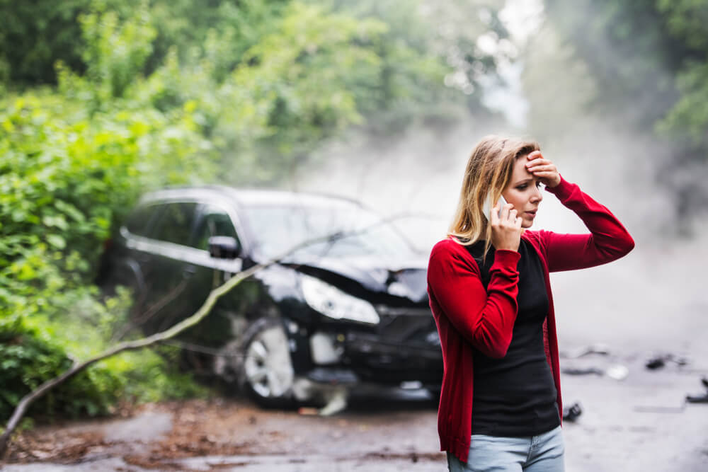 woman with phone on the side of the road with a crashed car with property damage insurance