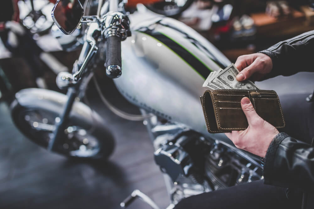 man getting money out of wallet to buy a used motorcycle on the background