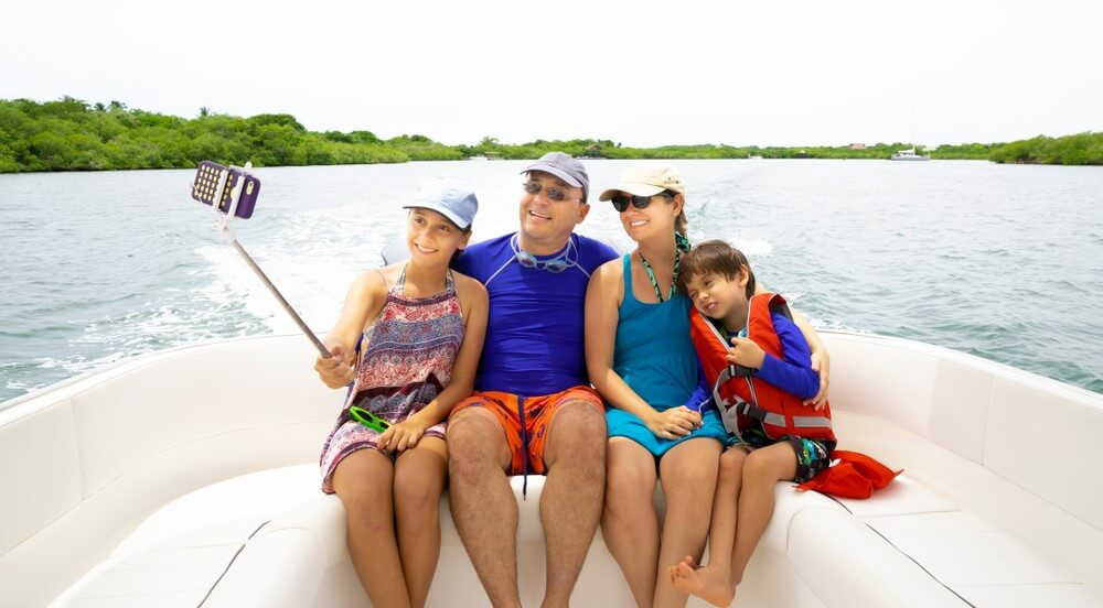 happy familiy taking a selfie on their boat with boat insurance