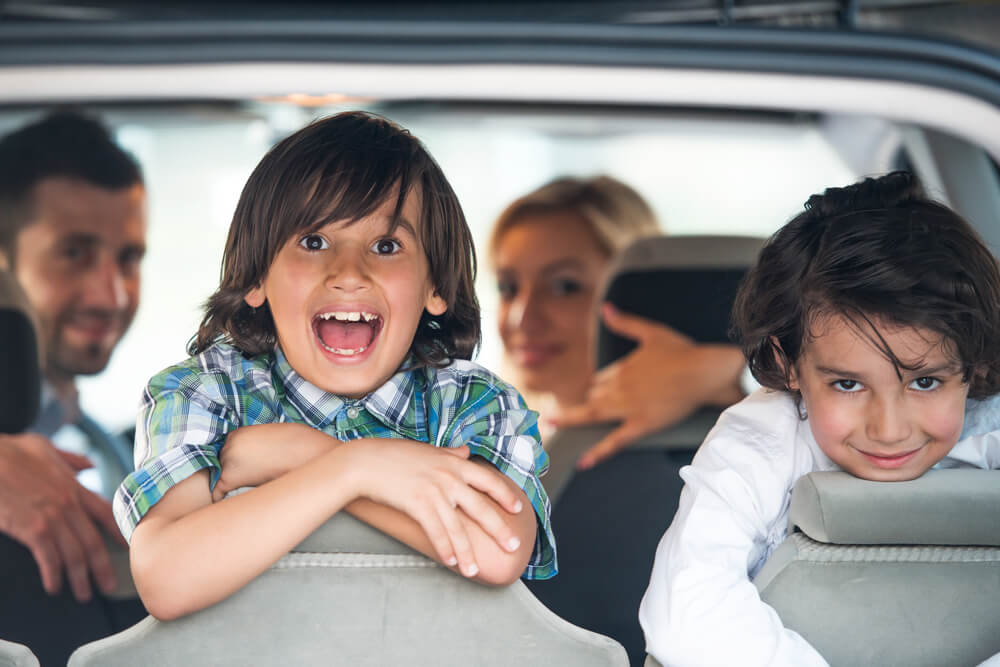 happy children inside car traveling with parents in the background