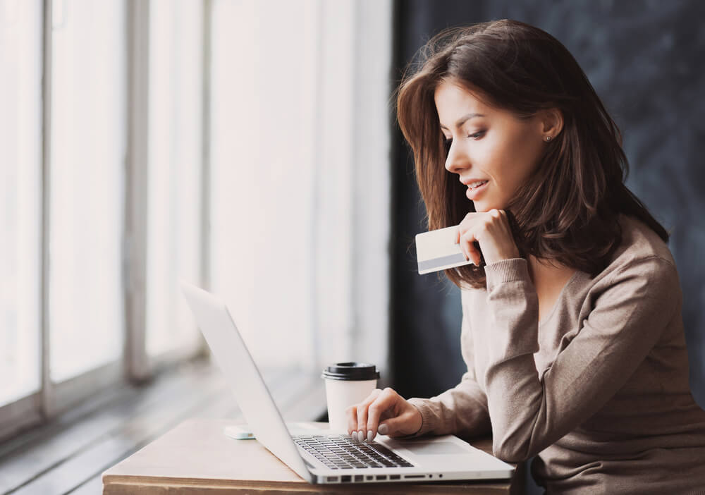 young woman in laptop online shopping with identity theft protection