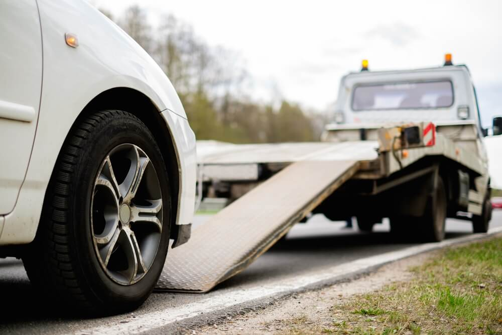 sideview of a car being  towed with a roadside assistance plan