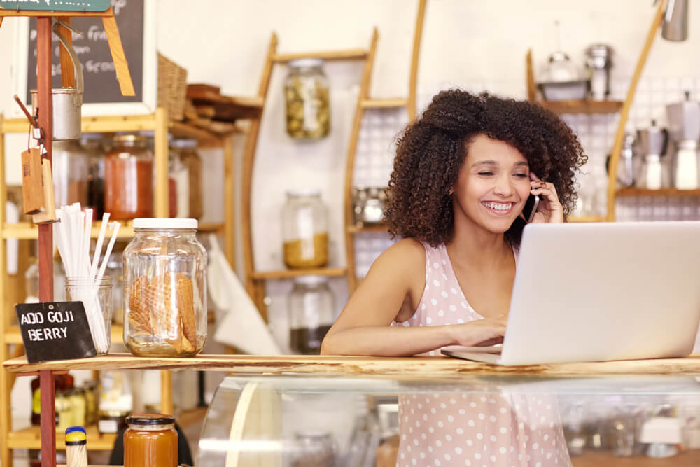 happy young woman in her coffee shop with a laptop and small business insurance
