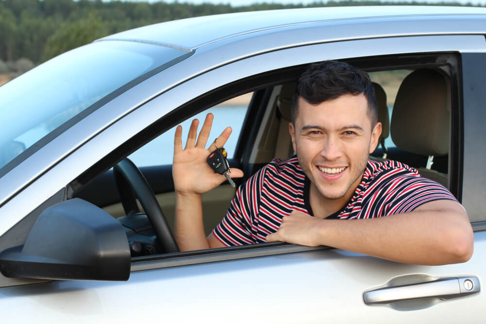 happy young man holding keys ready to buy a used car