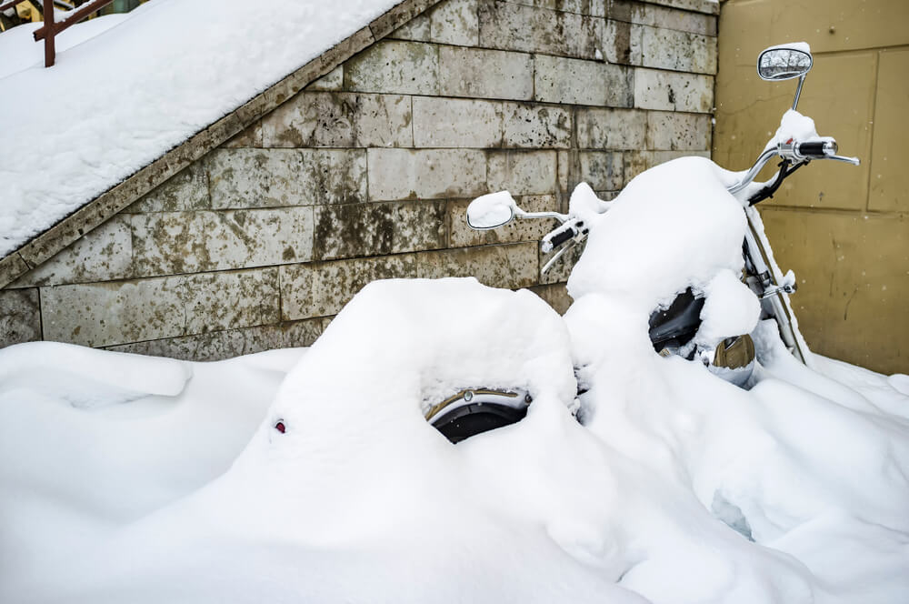 parked motorcycle buried in snow