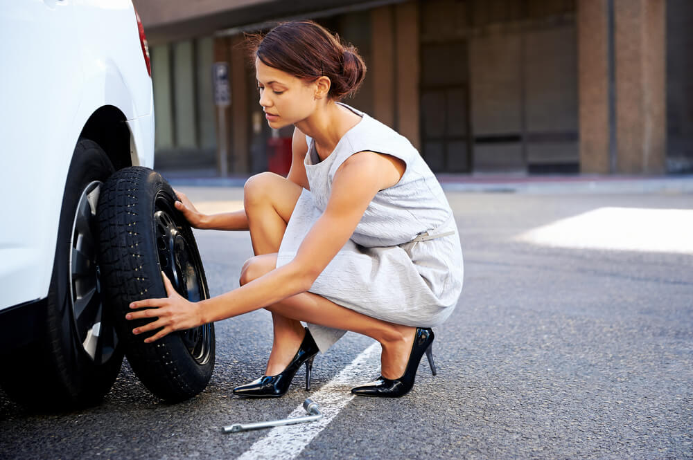 young hispanic business woman changing a tire