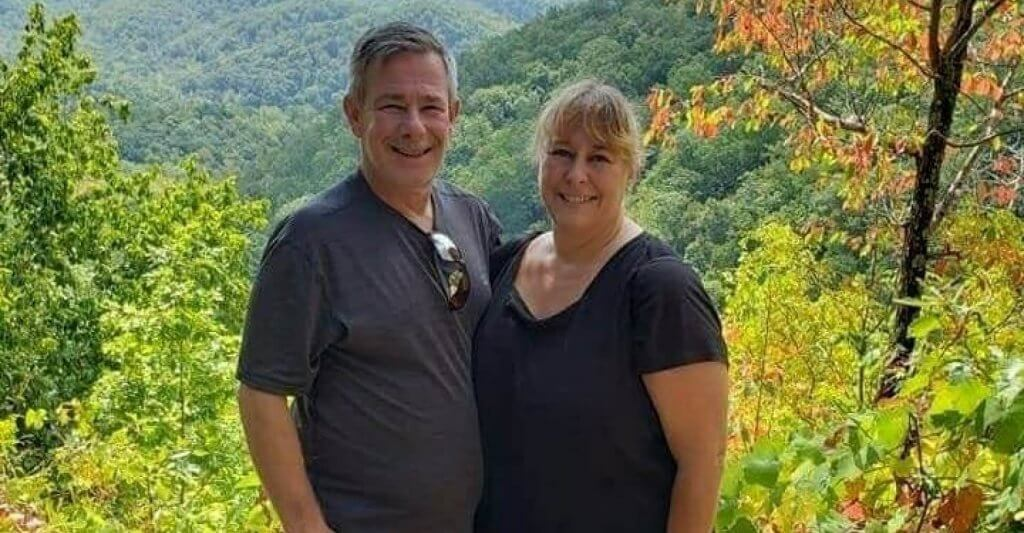 happy older couple with a nature background and the word love in fron