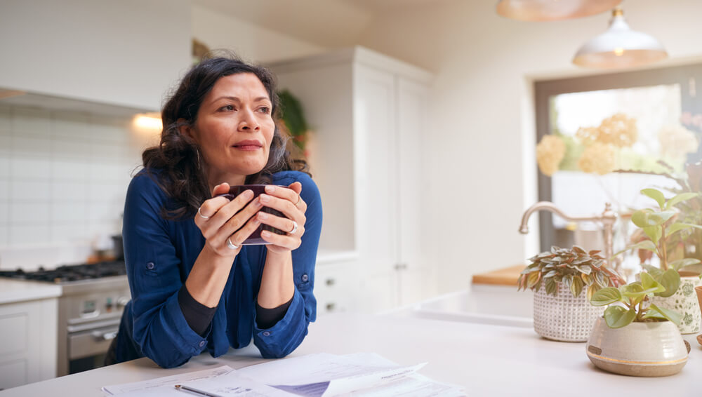 older hispanic woman in her ktichen wondering about the types of life insurance