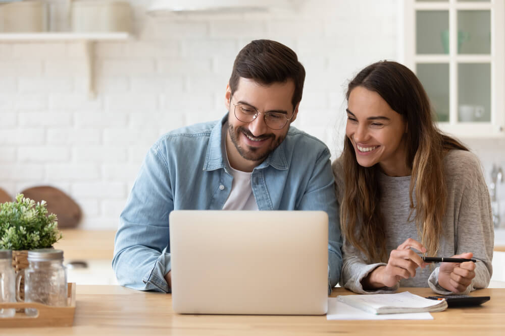 happy couple learning how to save money con car insurance in laptop