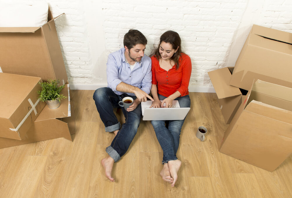 young happy couple on floor of home saving in insurance with laptop