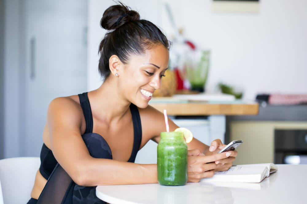 young atlethic woman smiling with green smoothie and looking at cell phone for cheap life insurance