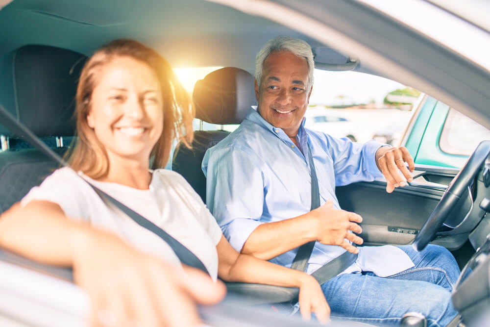 happy couple in car driving with insurance after a dui