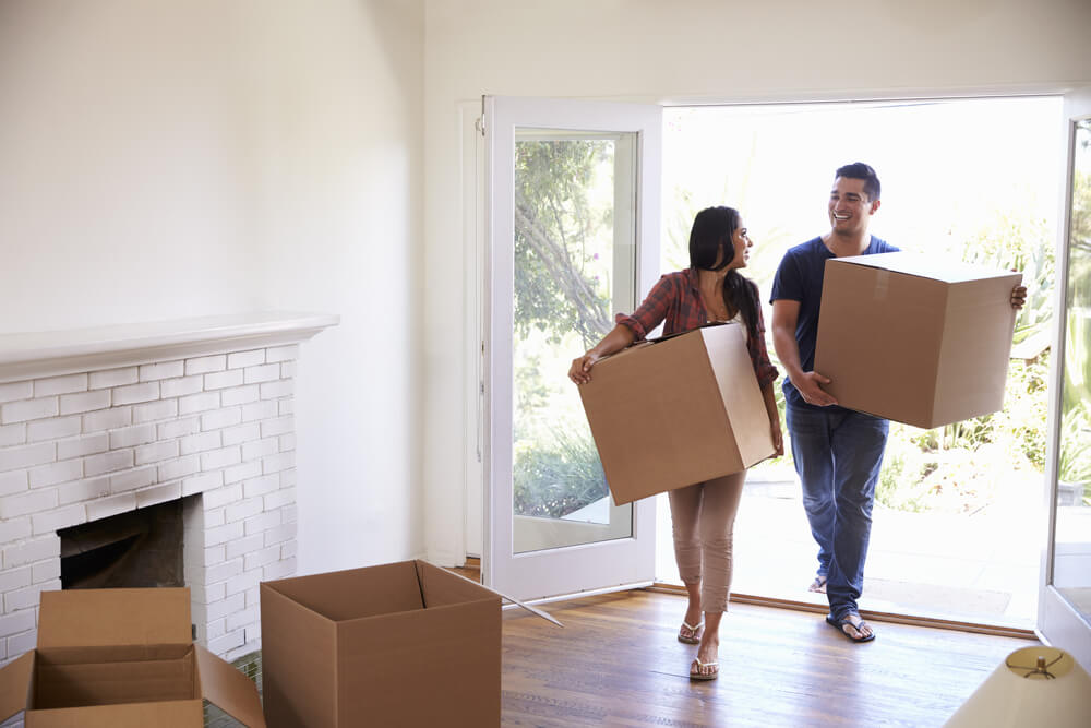 couple carrying boxes into their new home