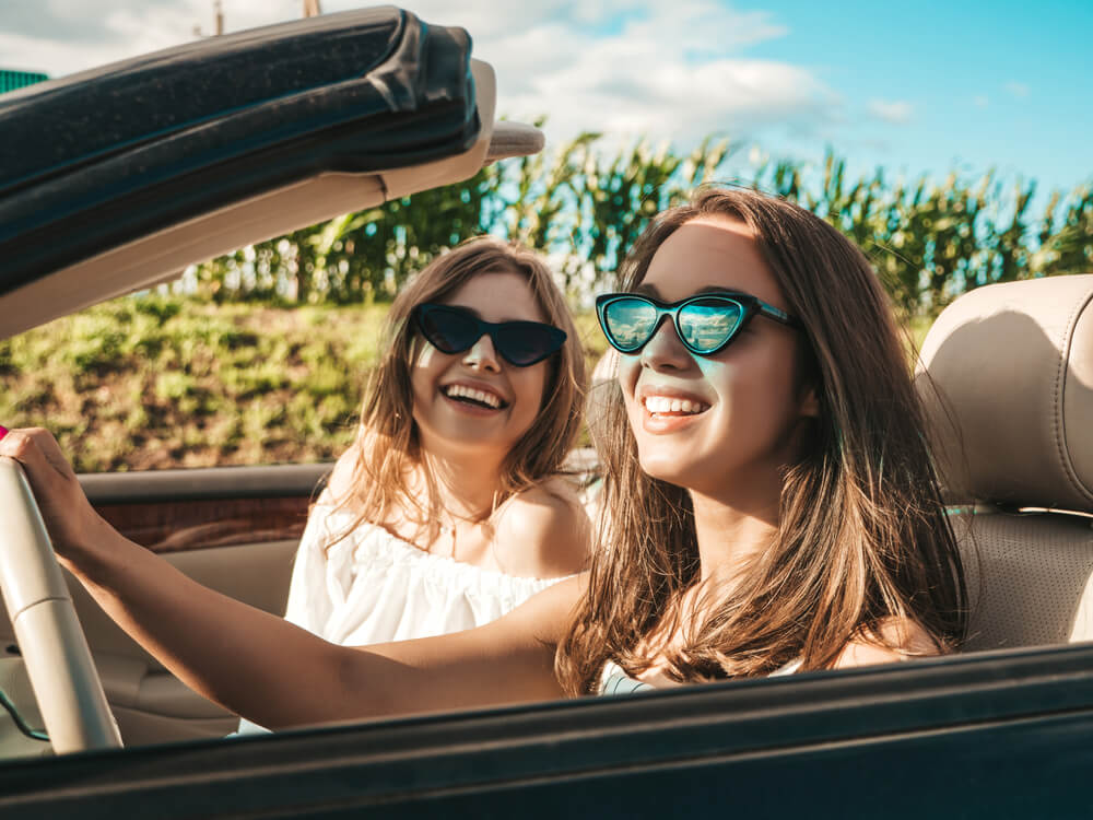 two happy women in convertible car