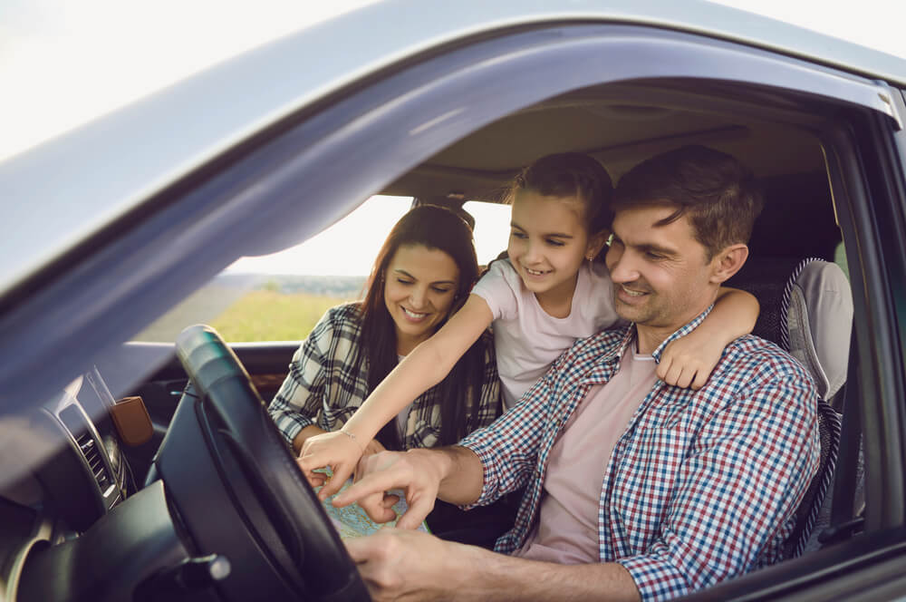 happy family with daughter in car with insurance deductible