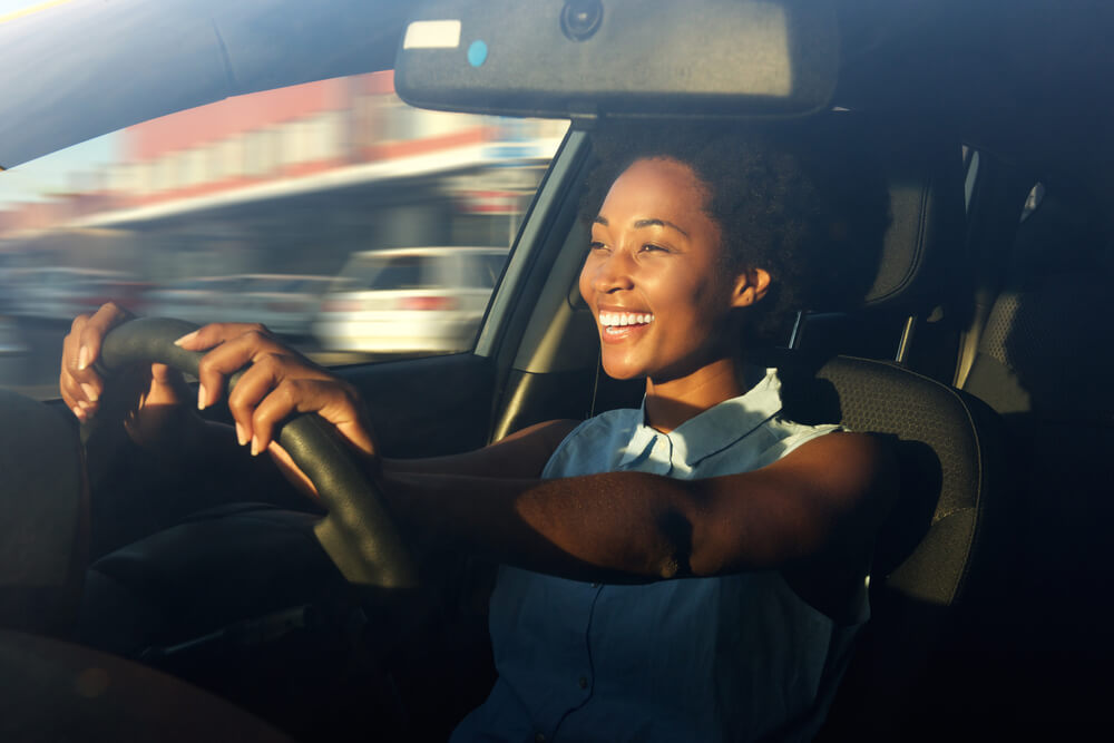 Portrait of smiling young african american college student driving car