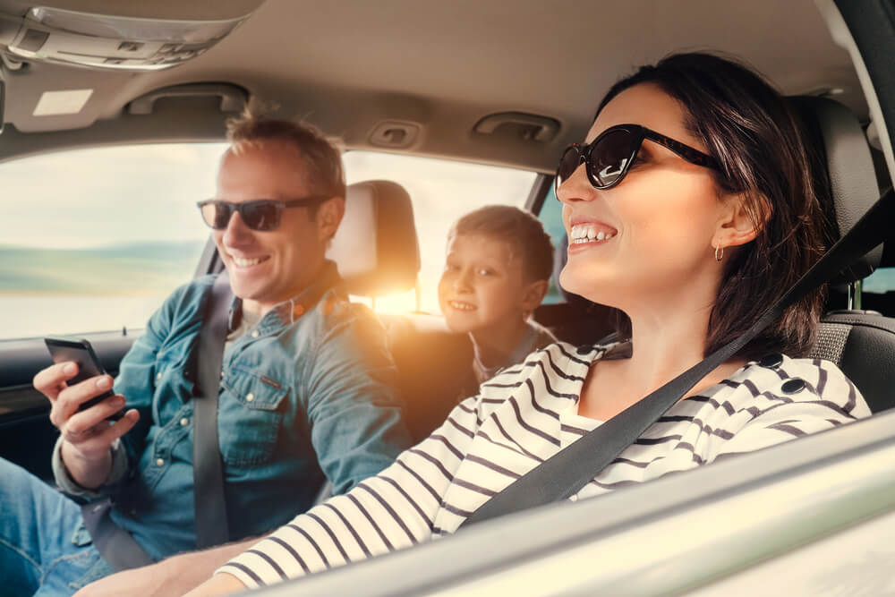 Happy family riding in a car with insurance