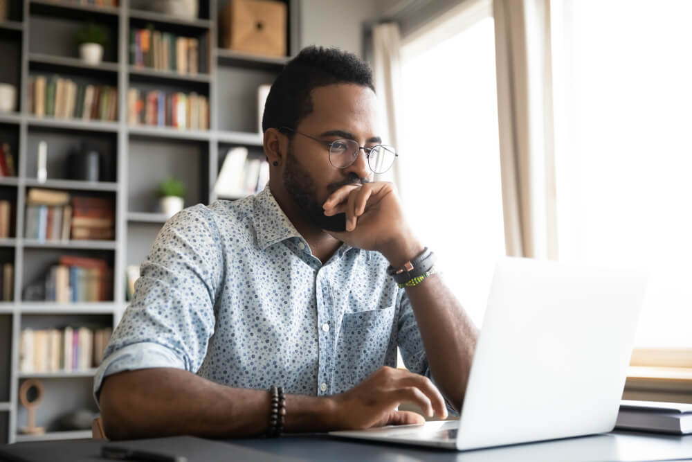 focused young african american man looking for car insurance in laptop
