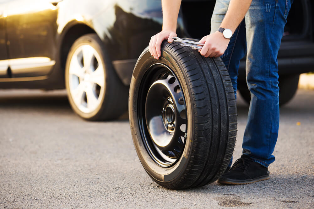 man holding an emergency spare tire with a car in the background
