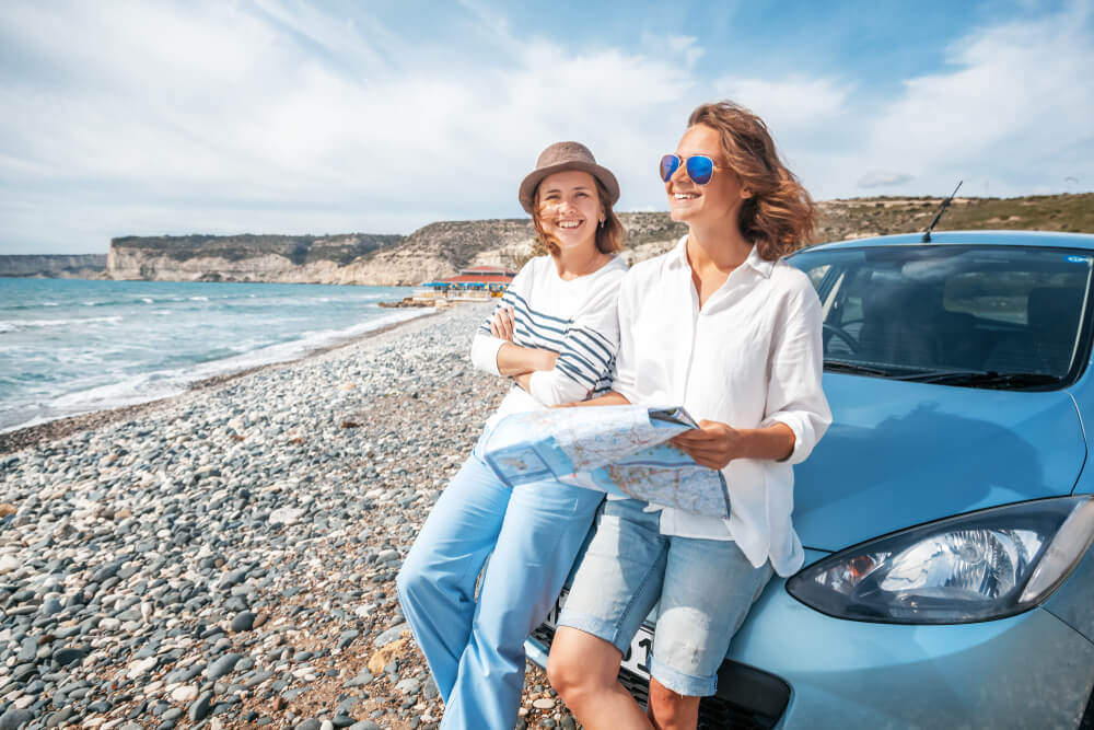 two women in car smiling and looking at map near the ocean