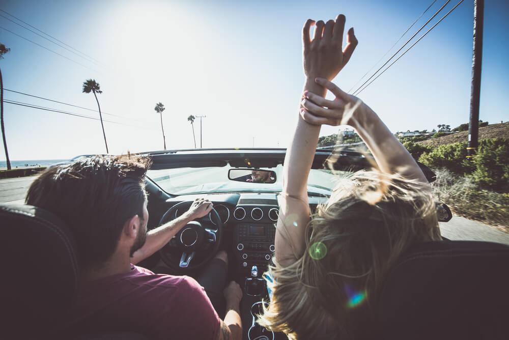 Couple driving in a convertible truck