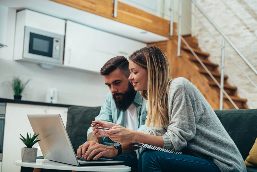 Shot of a young couple using a credit card and laptop for finding car insurance discounts