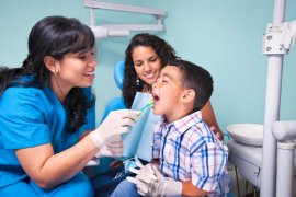 hispanic dentitst with boy patient