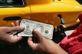 NEW YORK - AUGUST 23:  A taxi driver pays an attendant (R) for $20 worth of gasoline at a Lukoil gas station in the Chelsea neighborhood August 23, 2005 in New York City. The average price of gasoline rose 6.2 cents last week to a record average of $2.612 a gallon. Transportation Secretary Norman Mineta announced that automakers must increase the average fuel economy standards for light trucks beginning with 2011 models.  (Photo by Mario Tama/Getty Images)