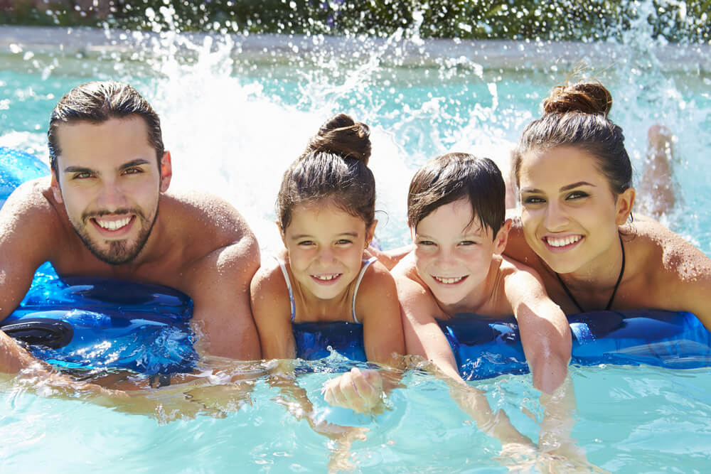 Portrait Of Family on Inflatable Raft in Swimming Pool