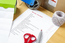 Picture of a moving checklist on a table, surrounded by labels, packaging tape, scissors, red marker pen, string, and a sealed box.