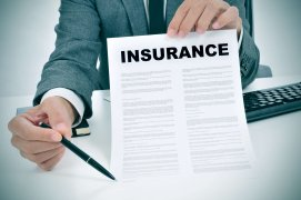 Insurance agent holding insurance document with pen requesting a signature from client