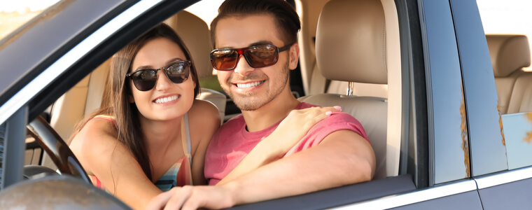 Young couple in car smiling becuase they saved a lot of money on their car insurance by switching to Freeway Insurance