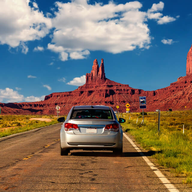 Photo of a road and cars driving toward the hills in Monument Valley, Arizona.