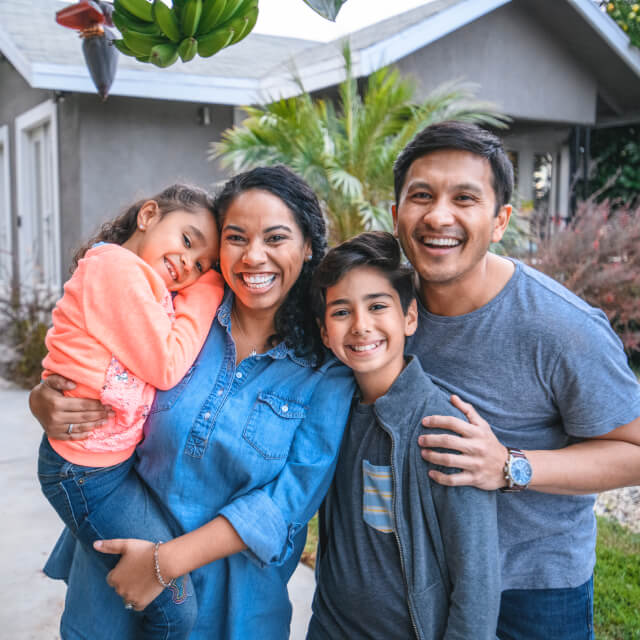 Portrait of a happy family composed by a man, a woman, a boy and a girl smiling in front of a house